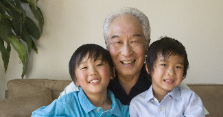 A grandfather smiles with two grandsons on his lap equally as happy.